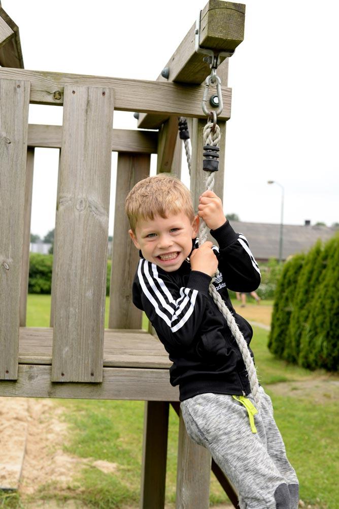 jongen hangend in de touwen